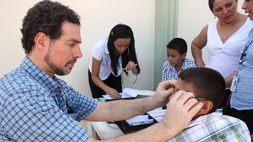 Jordan Kassalow sizes a new pair of eyeglasses for a boy in El Salvador.
