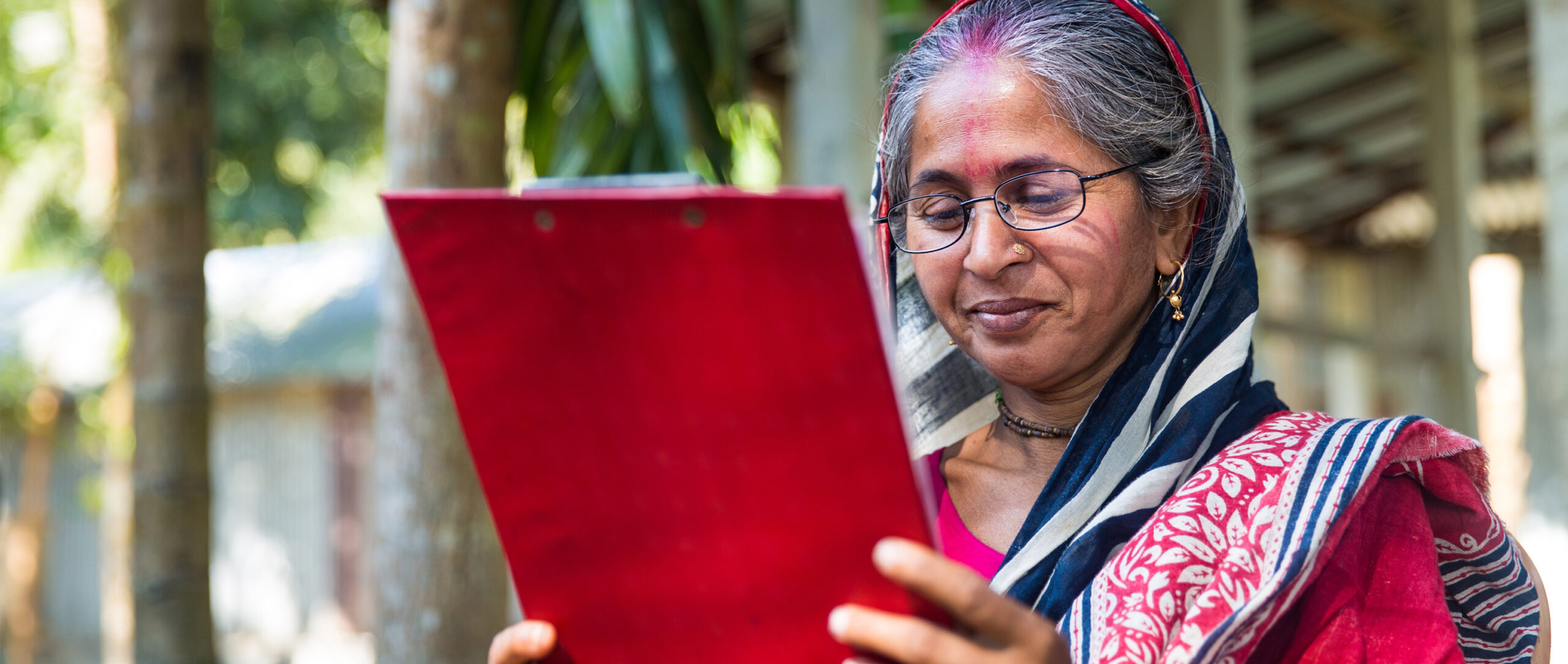 A woman in northern Bangladesh uses new reading glasses, purchased through VisionSpring's Reading Glasses for Improved Livelihoods (RGIL) program, to read clearly for the first time in years. The RGIL programs screens the vision of more than 1 million working age adults per year alongside BRAC community health workers in Bangladesh and Uganda.